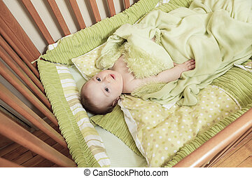 Overhead view of cute baby boy lying under blankets in wooden cr