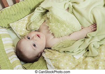 Overhead view of cute baby boy lying under cradle