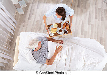 Nurse Serving Food To Senior Male Patient In Clinic