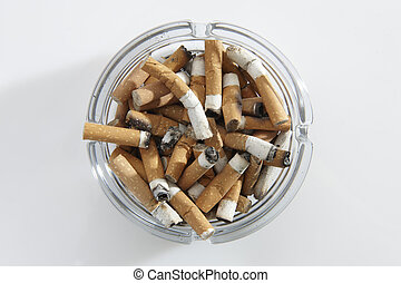 cigarette stubs - overhead view of glass ashtray full of...