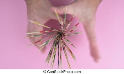overhead view of hands of person releasing a bundle of wooden mikado sticks or pick-up sticks