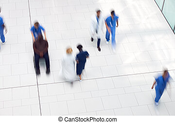 Overhead View Of Medical Staff Walking Through Lobby Of Modern Hospital Building With Motion Blur