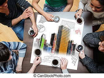 Overhead view of people sitting around table with painted city on sheet while having a cup of coffee