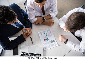 Overhead view of professional businessmen discussing charts at workplace, business concept