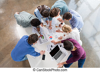 overhead view of professional businesspeople discussing and brainstorming together on workplace in office