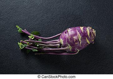 Overhead view of root vegetable on slate