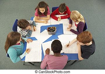Overhead View Of Schoolchildren Working Together At Desk