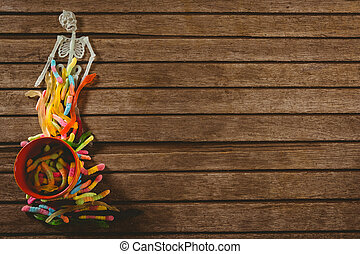 Overhead view of skeleton decoration with candies on wooden table