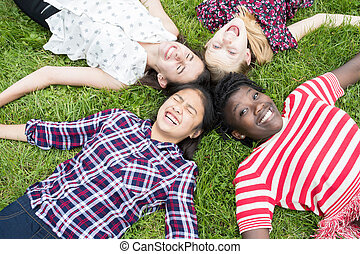 Overhead View Of Teenage Girl Friends Lying In Grass