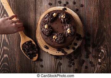 Overhead view of the chocolate cake, with chocolate chips, a hand on the spoon