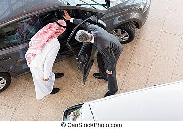 vehicle salesman selling a car to arabian man