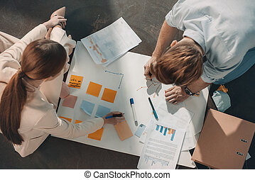 Overhead view of young business people sitting on floor and working with charts