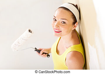 young woman holding painting roller