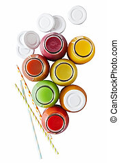 Overhead view on assorted different colored bottles of juice next to white caps and straws on isolated white background