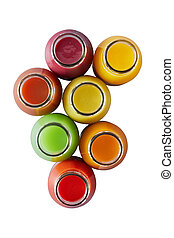 Overhead view on seven individual glass jars containing multicolored smoothies over white background