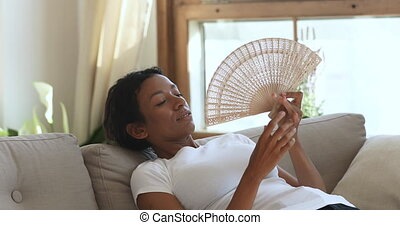 Overheated young african american lady suffering from high ...