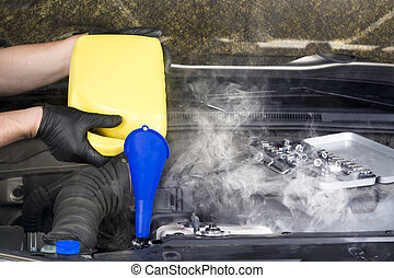 Overheater radiator - A mechanic pours engine coolant into...