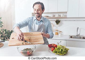 Overjoyed adult man cooking vegetable salad