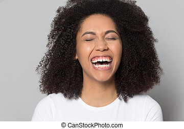 Overjoyed african american young woman laughing at joke.