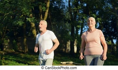 Overjoyed aged couple jogging in the park
