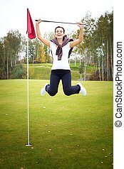 Overjoyed and smiling woman golf player in winner pose on...