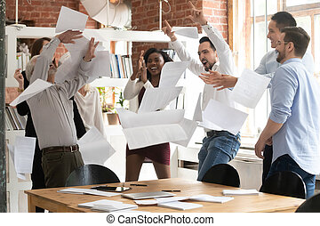 Overjoyed diverse employees throw papers celebrating success