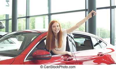 Overjoyed driver woman smiling and showing new key while...