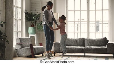 Overjoyed elder and younger sisters jumping in living room.