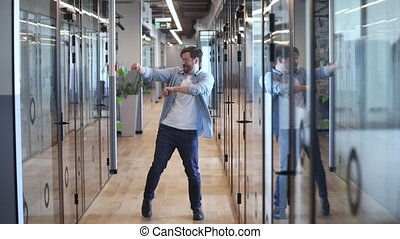 Overjoyed energetic young business man dancing alone in hallway celebrating reward promotion, work well done good result on friday, professional success, silly funny victory dance in office concept
