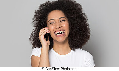 Overjoyed excited african american millennial lady talking on mobile phone.