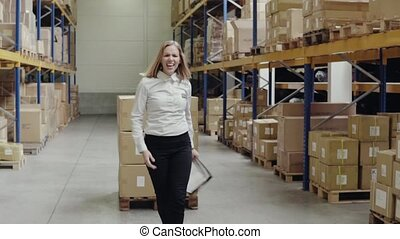 Overjoyed female worker or supervisor in a warehouse. -...