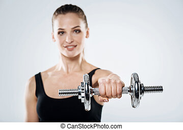 Overjoyed girl exercising with dumbbells on a grey background