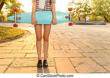 Overjoyed girl holding skateboard - Like it so much. Close...