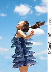 overjoyed girl in blue dress spin summer day