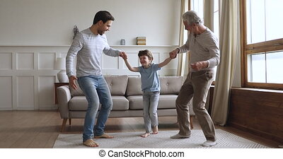 Overjoyed little child boy jumping with dad and grandfather.