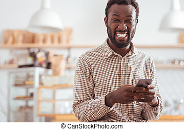 Overjoyed man laughing at his friends text messages