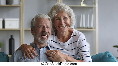 Overjoyed middle aged family couple relaxing on comfortable sofa.