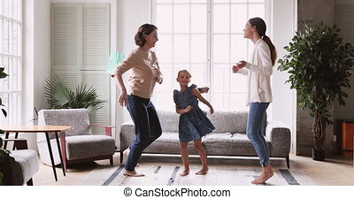 Overjoyed multigenerational family dancing barefoot in living room.
