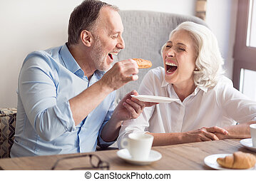 Overjoyed senior couple having lunch in the cafe