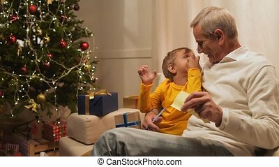 Overjoyed senior man and his grandson preparing Christmas presents