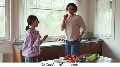 Overjoyed teen kid girl having fun with mom while cooking.