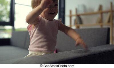 Overjoyed toddler sitting on the couch