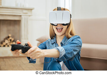 Overjoyed woman wearing virtual reality glasses and using remote control