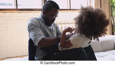Overjoyed young african american man playing with cute daughter.