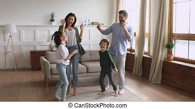 Overjoyed young couple dancing with happy small children.