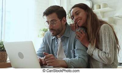 Lucky overjoyed happy young couple using looking at laptop computer excited by online bet bid win feel winners euphoric celebrating by internet lottery victory prize good news got new opportunity