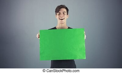 Overjoyed Young man in black shirt holding green key sheet poster gray background