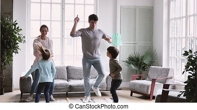 Overjoyed young parents dancing to music with preschool children.