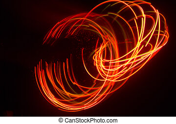 Overlaying wavy lines forming an abstract pattern on a dark background. Long exposure light background.