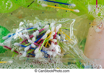 Bunch of colorful cotton swabs in plastic bag being